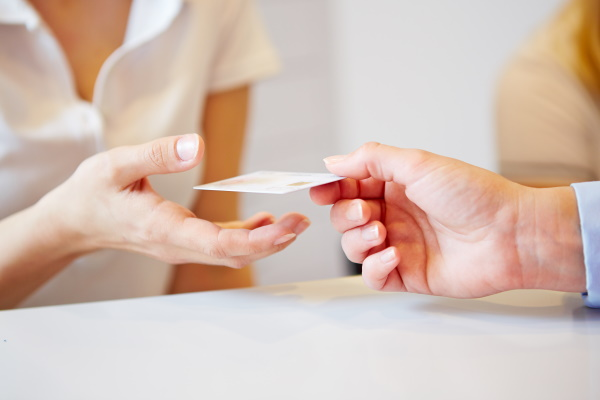 Hand of a patient giving smart card to doctors assistant